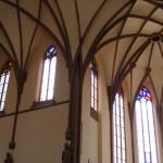 """Ansicht der Westseite. Bei allen Fenstern wurden die farblosen Rautenfelder mit einem seitlichen Zierstreifen versehen, und nur im Maßwerk - als Ergänzung zu noch vorhandenen Fragmenten - farbige Bleiverglasung eingesetzt. Die Sanierung  und Ausführng aller Fenster erfolgte durch """" Derix Glasstudios """" Taunusstein."""
